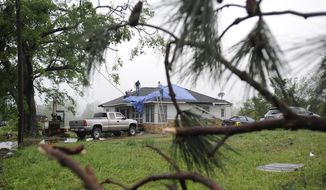 A pine tree toppled by an apparent tornado frames two men as they secure a tarp to the roof of a damaged house in Kimberly, Ala., on Tuesday, April 29, 2014. A severe storm caused damaged but no serious injuries in the community north of Birmingham late Monday. (AP Photo/Jay Reeves)