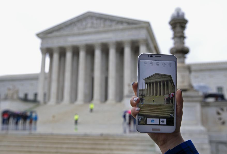 A Supreme Court visitor takes pictures with her cellphone outside the Supreme Court in Washington on April 29, 2014, during a hearing on whether police may search cellphones found on people they arrest without first getting a warrant. (Associated Press)