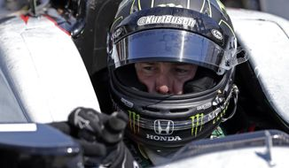Race driver Kurt Busch adjusts the mirror of his car during a break in practice at the Indianapolis Motor Speedway during the Rookie Orientation Program in Indianapolis, Tuesday, April 29, 2014. Busch will try to be the first driver in a decade to compete in IndyCar's Indianapolis 500 auto race and Sprint Cup's Coca-Cola 600 on the same day. (AP Photo/Michael Conroy)