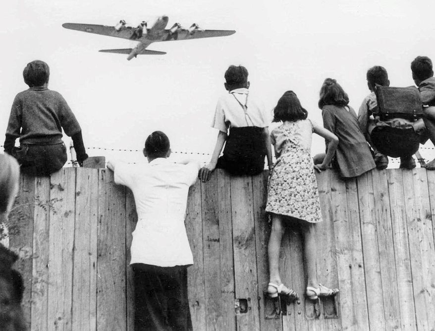 West Berlin children at Tempelhof Airport watch fleets of U.S. airplanes bringing in supplies to circumvent the Russian blockade in this undated file photo. The airlift began June 25, 1948, and continued for 11 months. (Associated Press/File)