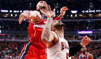 Wizards center Marcin Gortat blocks the shot of Bulls forward Carlos Boozer on Tuesday during the first half of Washington's series-clinching Game 5 victory. (associated press)