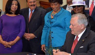 Martin Luther King III, his wife, Arndrea, sister Bernice and members of the General Assembly watch Governor Nathan Deal sign legislation related to the Martin Luther King Jr tribute statue  at the state Capitol Tuesday, April 29, 2014. Tuesday marks the last day the governor can sign bills into law.   (AP Photo/Atlanta Journal-Constitution, Kent D. Johnson)  MARIETTA DAILY OUT; GWINNETT DAILY POST OUT; LOCAL TV OUT; WXIA-TV OUT; WGCL-TV OUT