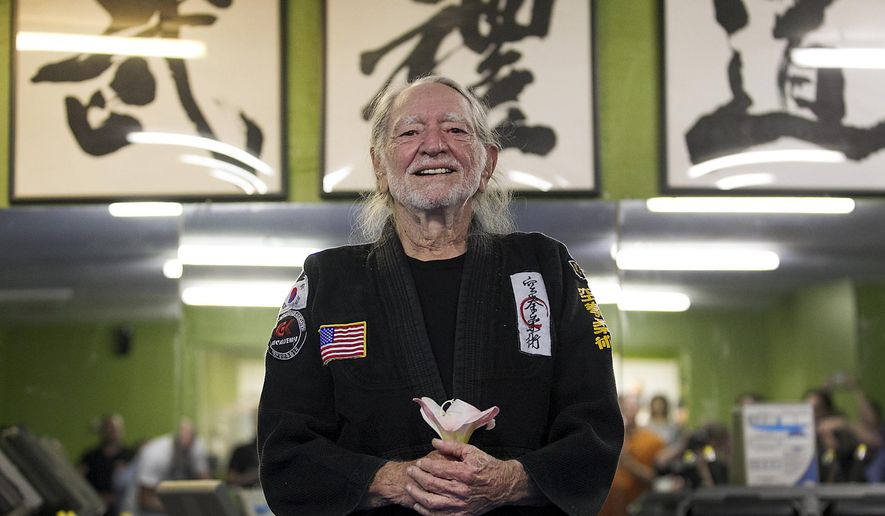 Willie Nelson, the country music icon who turns 81 this week, smiles as he receives his fifth-degree black belt in the martial art of Gong Kwon Yu Sul on Monday, April 28, 2014, in Austin, Texas.  (AP Photo/Austin American-Statesman, Ralph Barrera)