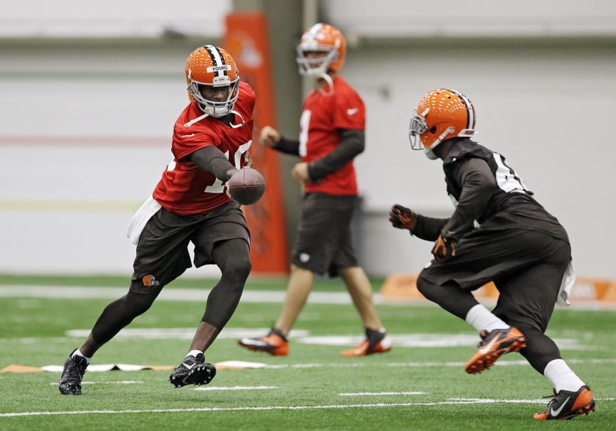 Cleveland Browns quarterback Vince Young, left, hands off to running back Ben Tate during a voluntary minicamp workout at the team's NFL football training facility in Berea, Ohio, Tuesday, April 29, 2014. (AP Photo/Mark Duncan)