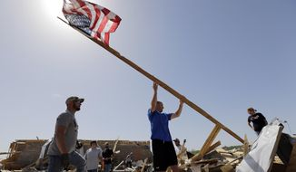 Justin Shaw, left, helps Nick Conway erect a flag pole at his home that was destroyed by a tornado, Monday, April 28, 2014, in Vilonia, Ark. (AP Photo/Eric Gay)