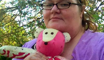 This April 2014 photo released by Kristine McCormick shows her posing in Indianapolis with a memorial teddy bear in honor of her daughter Cora, who died when she was five days old from an undetected congenital heart defect as she fed at her mother's breast on Dec. 6, 2009. (AP Photo/Kristine McCormick)