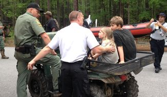 This photo provided by the National Park Service, rescue personnel attend to Dakota Kimbler, 10 and his sister Jade Kimbler, 6, after they were lost with their father inside Congaree National Park, Tuesday, April 29, 2014 in Hopking, SC. The family was lost for more than two days in the vast woods and swaps of the park. They are all listed in stable condition. (AP Photo/National Park Service)