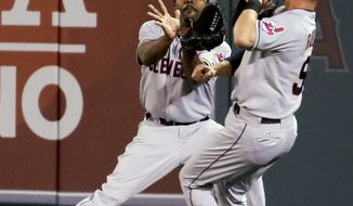 Cleveland Indians center fielder Michael Bourn, left, almost collides with left fielder Ryan Raburn while catching a fly ball hit by Los Angeles Angels' Ian Stewart during the seventh inning of a baseball game in Anaheim, Calif., Monday, April 28, 2014. (AP Photo/Chris Carlson)