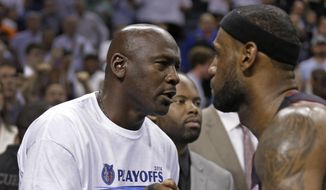 Charlotte Bobcats owner Michael Jordan, left, shakes hands with Miami Heat's LeBron James, right, after Game 4 of an opening-round NBA basketball playoff series in Charlotte, N.C., Monday, April 28, 2014. The Heat won 109-98, sweeping the series. (AP Photo/Chuck Burton)