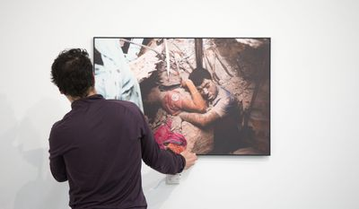"Josh Harris hangs Taslima Akhter's World Press Photo prize-winning image titled ""Final Embrace,"" Monday, April 28, 2014, at Drexel University in Philadelphia. The 2014 World Press Photo exhibit is scheduled to be on display from May 1 to May 21. (AP Photo)"