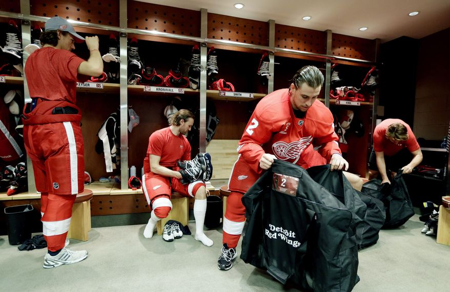 Detroit Red Wings defensemen from left, Danny Dekeyser, Niklas Kronwall of Sweden, Brendan Smith and Jakub Kindl pack their bags after participating in the team photo at Joe Louis Arena in Detroit, Tuesday, April 29, 2014. The Red Wings were eliminated by the Boston Bruins in the first round of the Stanley Cup hockey playoffs. (AP Photo/Carlos Osorio)