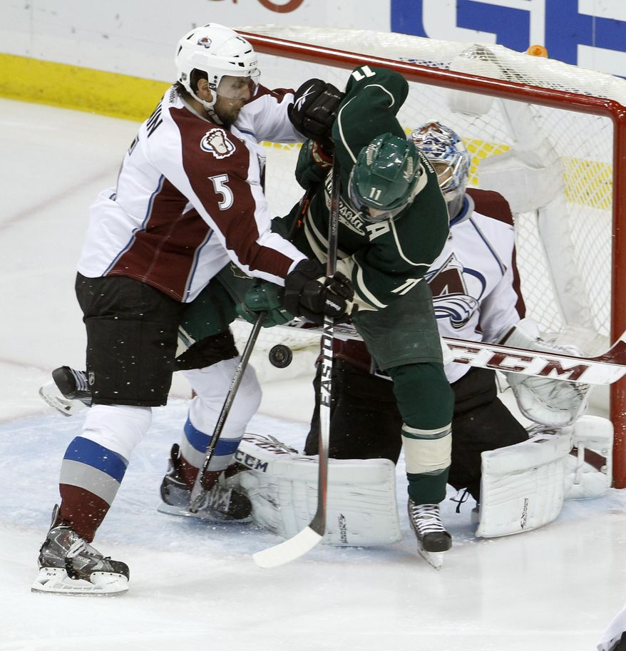 A shot by Minnesota Wild defenseman Ryan Suter gets past Wild left wing Zach Parise (11) and Colorado Avalanche defenseman Nate Guenin (5) and goalie Semyon Varlamov, right, of Russia, for a goal during the first period of Game 6 of an NHL hockey first-round playoff series in St. Paul, Minn., Monday, April 28, 2014. (AP Photo/Ann Heisenfelt)