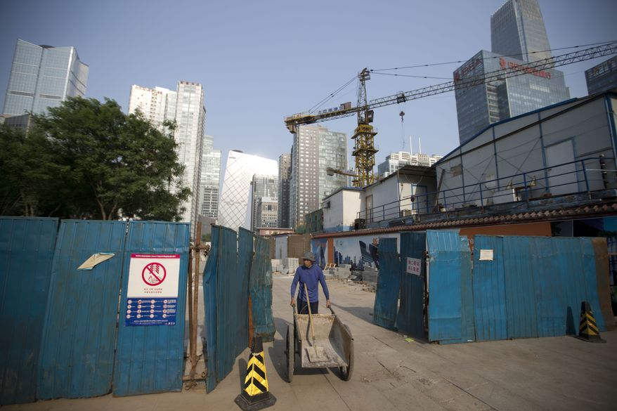 A worker pushes a cart as he walks out from a construction site at the Central Business District in Beijing, China Tuesday, April 29, 2014. The International Monetary Fund raised its economic growth forecast for China on Monday but warned that its financial system faces risks due to the rapid expansion of debt. (AP Photo/Andy Wong)