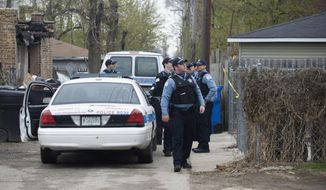 In this Monday, April 28, 2014 photo, police stand outside a residence in Chicago after 14-year-old girl was fatally shot and another girl wounded in the Back of the Yards neighborhood in Chicago. No arrests have been made in the shootings, but police said late Monday that they were interviewing a person of interest. (AP Photo/Sun-Times Media, Richard A. Chapman)  MANDATORY CREDIT, MAGS OUT, NO SALES