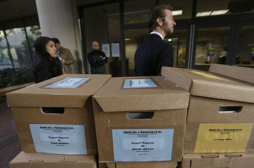Clerks stand behind boxes containing documents related to the Apple Inc. versus Samsung case outside of a federal courthouse in San Jose, Calif., Monday, April 28, 2014. A federal court has delayed by a day closing arguments in the Apple and Samsung trial because of an appeals court ruling in another case on a related patent issue. Dueling expert witnesses were called back to the stand Monday in a San Jose federal courtroom to discuss whether the ruling in a legal dispute between Apple and Motorola has any effect on the Apple and Samsung trial. Lawyers will now deliver closing arguments Tuesday. (AP Photo/Jeff Chiu)