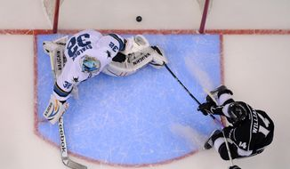 Los Angeles Kings right wing Justin Williams, right, scores San Jose Sharks goalie Alex Stalock looks on during the first period in Game 6 of an NHL hockey first-round playoff series, Monday, April 28, 2014, in Los Angeles. (AP Photo)