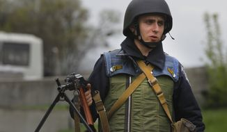 Ukrainian government soldier holds his machine gun as he guards a checkpoint near the village of Dolina, 30 kilometers (18 miles) from Slovyansk, eastern Ukraine, Tuesday, April 29, 2014. The European Union on Tuesday released the names of 15 new targets of sanctions because of their roles in the Ukraine crisis. The list includes Gen. Valery Gerasimov, chief of the Russian General Staff and first deputy defense minister, and Lt. Gen. Igor Sergun, identified as head of GRU, the Russian military intelligence agency. (AP Photo/Sergei Grits)