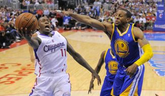 Los Angeles Clippers guard Jamal Crawford, left, puts up a shot as Golden State Warriors forward Andre Iguodala defends during the second half in Game 5 of an opening-round NBA basketball playoff series, Tuesday, April 29, 2014, in Los Angeles. The Clippers won 113-103. (AP Photo)