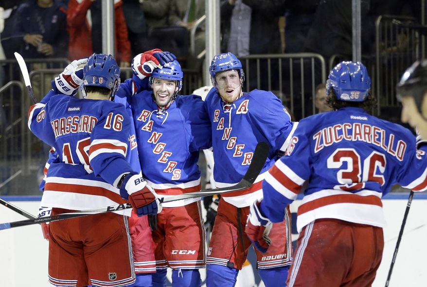New York Rangers' Benoit Pouliot (67) celebrates with teammates Mats Zuccarello (36), Adam Hall (18) and Derick Brassard (16) after scoring a goal during the second period against the Philadelphia Flyers in Game 7 of an NHL hockey first-round playoff series on Wednesday, April 30, 2014, in New York. (AP Photo)