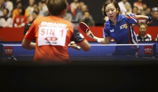 Yang Hae-un, right, of South Korea returns the ball during her round robin match of the World Team Table Tennis Championships against Singapore's Feng Tianwei, left, in Tokyo, Wednesday, April 30, 2014.  (AP Photo/Eugene Hoshiko)