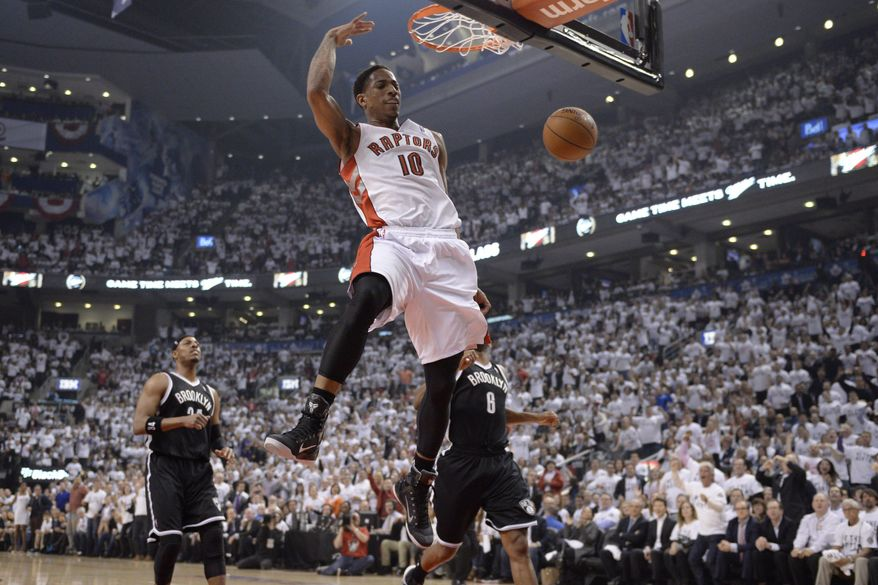 Toronto Raptors' DeMar DeRozan (10) dunks as Brooklyn Nets' Paul Pierce (34) and Deron Williams (8) look on during the first half of Game 5 of the opening-round NBA basketball playoff series in Toronto, Wednesday, April 30, 2014. (AP Photo/The Canadian Press, Frank Gunn)