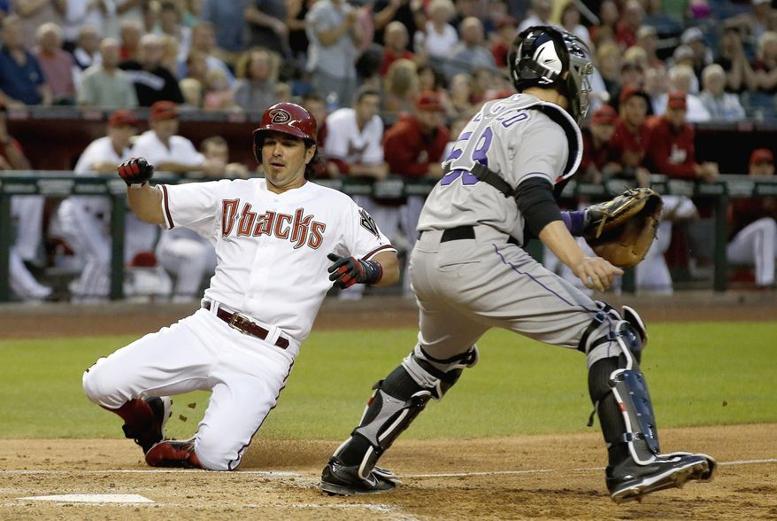 Arizona Diamondbacks' Eric Chavez, left, slides into home plate to score a run as Colorado Rockies' Jordan Pacheco waits for a late throw during the second inning of a baseball game on Tuesday, April 29, 2014, in Phoenix. (AP Photo/Ross D. Franklin)