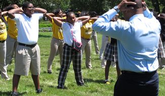 Rep. Wesley Bishop, D-New Orleans, right, exercises with dozens of students from his district outside the Louisiana Capitol, in an effort to promote physical fitness on Wednesday, April 30, 2014, in Baton Rouge, La. (AP Photo/Melinda Deslatte)
