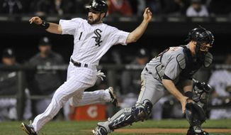 Chicago White Sox's Adam Eaton (1), crosses home plate safely as Detroit Tigers catcher Bryan Holaday waits for the throw during the third inning of a baseball game, Tuesday, April 29, 2014, in Chicago. (AP Photo/Paul Beaty)