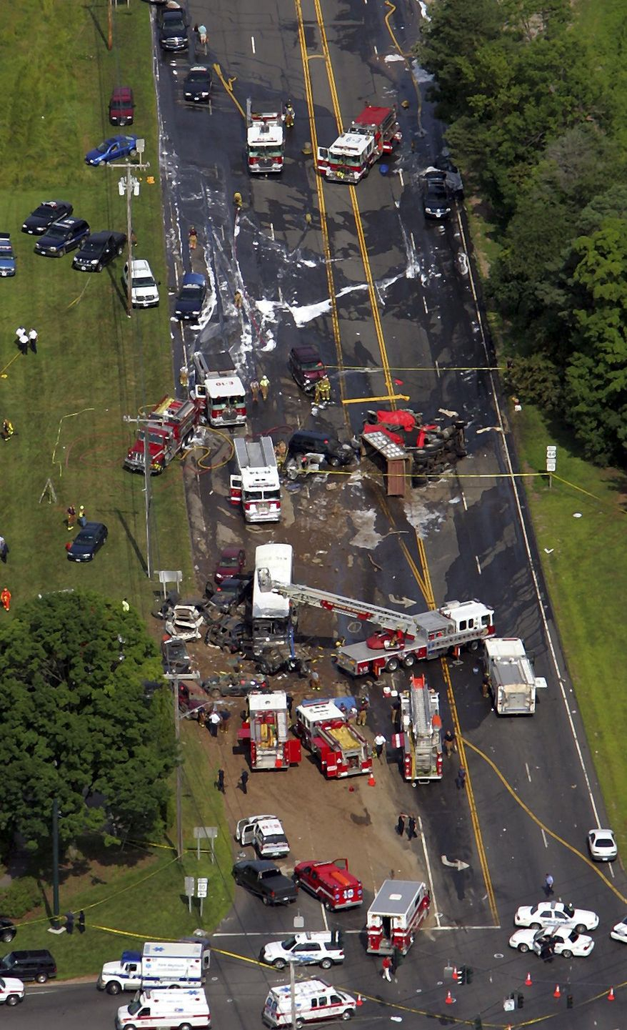 FILE - In this July 29, 2005 file photo, emergency personnel and vehicles work an accident in Avon, Conn. Lawyers for victims of the wreck, which killed four people and injured 19, argued before the state Supreme Court Wednesday, April 30, 2014, to have claims against the state Department of Transportation adjudicated before a jury. The victims have said there weren't adequate safety precautions, like a runaway truck ramp for the steep road. The department denies the road was defective and claims government immunity. (AP Photo/Bob Child, File)