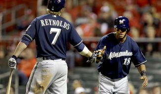 Milwaukee Brewers' Khris Davis, right, is congratulated by teammate Mark Reynolds, left, after scoring on a single by Lyle Overbay during the 11th inning of a baseball game against the St. Louis Cardinals, Tuesday, April 29, 2014, in St. Louis. (AP Photo/Jeff Roberson)