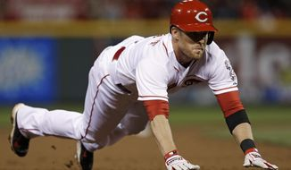 Cincinnati Reds' Zack Cozart dives into third base with a triple off Chicago Cubs starting pitcher Jeff Samardzija in the sixth inning of a baseball game, Tuesday, April 29, 2014, in Cincinnati. Cozart scored later in the inning. (AP Photo)