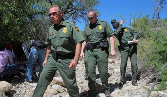 ** FILE ** U.S. Border Patrol Tucson Sector Chief Manuel Padilla, left front, walks with other agents and media during a tour in the Buenos Aires National Wildlife Refuge, Wednesday, April 30, 2014, near Sasabe, Ariz. Padilla and other Border Patrol officials spent the day discussing the dangers for immigrants trying to cross the border illegally from Mexico into the U.S. (AP Photo/Brian  Skoloff)