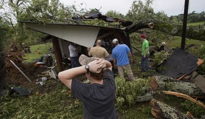 People work on clearing a tree off a shed after a storm in Smiths Station, Ala., Tuesday, April 29, 2014. A dangerous storm system that spawned a chain of deadly tornadoes over two days flattened homes and businesses, and killed dozens from the Midwest to the Deep South. (AP Photo/Opelika-Auburn News, Albert Cesare)