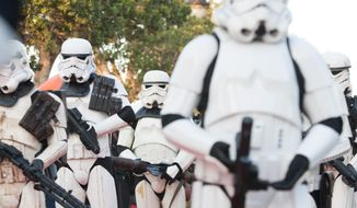 """""""Star Wars"""" fan dressed as stormtroopers parade along Tunis' stately, tree-lined Bourguiba Avenue, in Tunisia, Wednesday, April 30, 2014. (AP Photo/Aimen Zine) ** FILE **"""