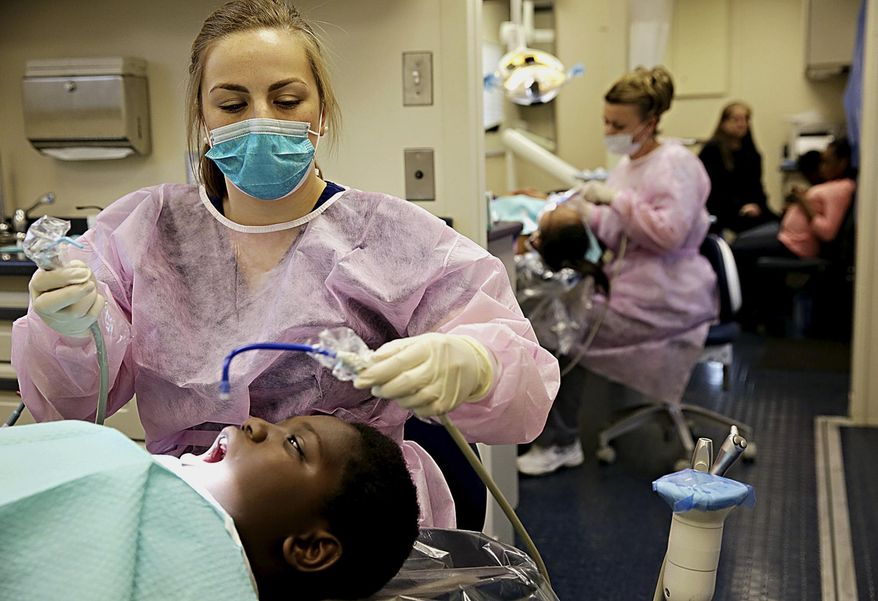 In this April 8, 2014 photo, Dr. Erica Zolnierczyk, left, cleans 11-year-old Maurice Bankston's teeth during a dental check-up onboard the Will County Community Health Center Mobile Dental Services vehicle in University Park, Ill. The Will County Health Department offers dental service to anyone in the county their van can reach. (AP Photo/The Herald-News, Rob Winner)
