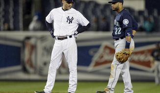 New York Yankees' Derek Jeter talks to Seattle Mariners second baseman Robinson Cano during the eighth inning of a baseball game Tuesday, April 29, 2014, in New York. (AP Photo)