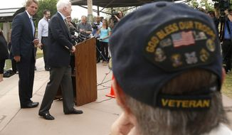 **FILE** With Vietnam military veteran Chuck Tharp (right) listening in, Arizona Republican Sens. John McCain (second from left) and Sen. Jeff Flake (left) finish up a news conference to discuss recent reports that dozens of VA hospital patients in Arizona may have died while awaiting medical care in the Phoenix VA Health Care System, adjacent to the VA Hospital on April 18, 2014, in Phoenix. Last week's disclosures by current and former Department of Veterans Affairs employees is leading to investigations by the House Committee on Veterans Affairs and the Inspector General for the VA are looking into not only the deaths, but allegations of falsified record keeping and medical reporting. (Associated Press)