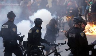 FILE -- In this May 1, 2013, file photo, protesters react as a police flash-bang grenade goes off during a May Day march that began as an anti-capitalism protest and turned into demonstrators clashing with police in downtown Seattle. May Day has turned violent recently in Seattle, where last year police arrested 18 people from a crowd that pelted them with rocks and bottles. A year earlier masked marchers dressed in black broke windows and doors on downtown banks and stores and tried to set a fire at a federal building. (AP Photo/Ted S. Warren, File)