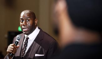"Businessman and former NBA star Magic Johnson speaks to an audience member at an event in Saginaw, Mich., Tuesday, April 29, 2014. Johnson returned to Saginaw for the third annual ""Magic of a Promise"" fundraiser for the Saginaw Promise Scholarship. (AP Photo/The Saginaw News, Neil Barris)"