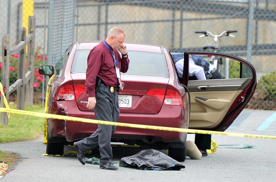 """Police officials search a car located at the scene of the shooting that took place at a FedEx facility in Kennesaw, Ga., on Tuesday, April 29, 2014.  A shooter described as being armed with an assault rifle and having bullets strapped across his chest """"like Rambo"""" opened fire Tuesday morning at a FedEx station outside Atlanta, wounding at least six people before police found the suspect dead from an apparent self-inflicted gunshot.  (AP Photo/Atlanta Journal-Constitution, Brant Sanderlin)  MARIETTA DAILY OUT; GWINNETT DAILY POST OUT; LOCAL TV OUT; WXIA-TV OUT; WGCL-TV OUT"""