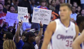 Fans hold up signs as Los Angeles Clippers forward Blake Griffin looks on during the second half in Game 5 of an opening-round NBA basketball playoff series against the Golden State Warriors, Tuesday, April 29, 2014, in Los Angeles. The Clippers won 113-103. (AP Photo)