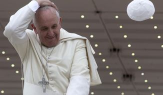 A gust of wind blows away Pope Francis' cap as he leaves at the end of his weekly general audience, at the Vatican, Wednesday, April 30, 2014. (AP Photo/Andrew Medichini)