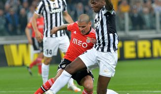 Juventus midfielder Paul Pogba, of France, right, challenges for the ball with Benfica defender Maxi Pereira during the Europa League semifinal second leg soccer match between Juventus and Benfica at the Juventus stadium, in Turin, Italy, Thursday, May 1, 2014. (AP Photo/ Massimo Pinca)