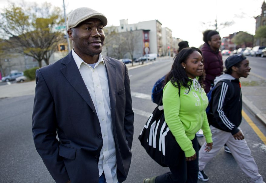 """In a photograph taken Wednesday, April 23, 2014, Dr. Kai Smith, former gang member and now founder and Executive Director of GRAAFICS (Gang Diversion, reentry and Absent Father Intervention Center), walks with GRAAFICS students Tyasia Blair, 16, of East New York, Devon Collins, 16, of East New York, and Jamal Williams, 18 (background right) in the Brownsville neighborhood of Brooklyn, N.Y. They along with other students at the nearby Brooklyn Collegiate High School enter the GRAAFICS program if they have been part of a """"crew,"""" and work to stay focused on getting on with their educations and lives without being part of a neighborhood crew. (AP Photo/Craig Ruttle)"""