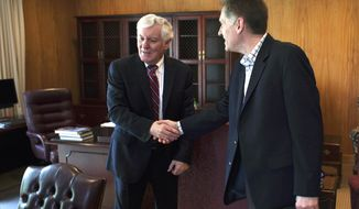 Southern Illinois University President Glenn Poshard, left, shakes hands with incoming SIU president Randy Dunn, on Wednesday, April 30, 2014, in Carbondale, Ill., on Poshard's last day on the job. Poshard, a former congressman and Illinois gubernatorial candidate, officially retired Wednesday but will stay on through June as a consultant to his successor.  (AP Photo/The Southern, Steve Matzker)