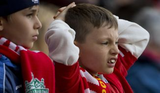 A young Liverpool supporter watches as his team is beaten by Chelsea in their English Premier League soccer match at Anfield Stadium, Liverpool, England, Sunday April 27, 2014. (AP Photo/Jon Super)