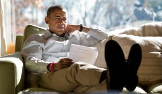 President Obama reads briefing material while meeting with advisers inside his cabin at Camp David in 2012. Compared with President Bush, seen right with first lady Laura Bush on a 4-mile walk, Mr. Obama seldom uses the presidential retreat. On weekends, he often opts to play golf. The Bushes founds the grounds to be a good place for family. (WHITE HOUSE PHOTOGRAPHS)