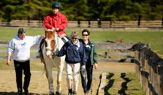 Step by Step: Mee Jee Yeargain, who is blind and autistic, gets some help from an equine friend and volunteers at Maryland Therapeutic Riding. (Andrew Harnik/The Washington Times)