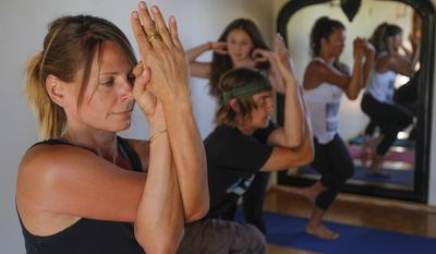 Jennifer Miller, left, follows the instructions of yoga teacher Jaysea DeVoe, at Bergamot Spa & Boutique in Encinitas, Calif.,  on Tuesday, April 29, 2014.  DeVoe, 12, is one of the nation's youngest certified yoga instructors.  She recently completed a five-month, 200-hour certification program with two girlfriends, ages 13 and 15, and has joined the staff at Bergamot Spa in her hometown. (AP Photo/U-T San Diego, Hayne Palmour IV) MANDATORY CREDIT   NO SALES; COMMERCIAL INTERNET OUT