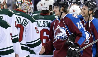 Colorado Avalanche center Nathan MacKinnon (29) greets Minnesota Wild goalie Ilya Bryzgalov (30) of Russia following Game 7 of an NHL hockey first-round playoff series on Wednesday, April 30, 2014, in Denver. Minnesota won 5-4 to win the series. (AP Photo/Jack Dempsey)